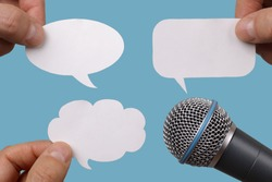 Conference, interview or social media concept with microphone and blank speech bubbles