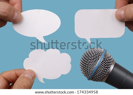 Photo of  Conference, interview or social media concept with microphone and blank speech bubbles