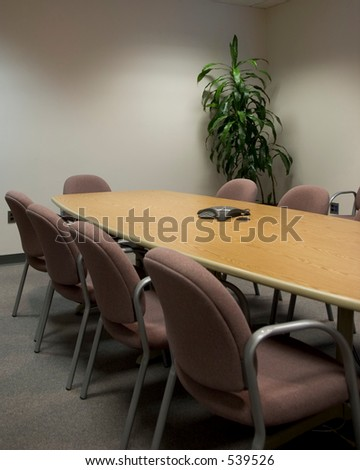 Conference room - vertical shot. Tables surround a long conference table with a plant in the corner.