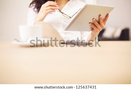 Conference table with a woman reading something on her digital tablet