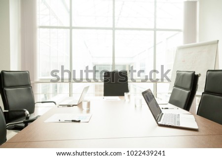 Conference table with laptops, documents and chairs in office of modern contemporary business center, big corporate boardroom interior with large window, empty light meeting room work space concept