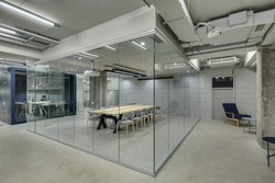 Conference zone in the office in a loft style with brick walls and concrete columns. Zone has a wooden table with gray chairs and glass walls. Behind it there is blue meeting zone with glass doors.