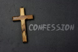 Confession word written on black background with wooden cross. Christian symbol