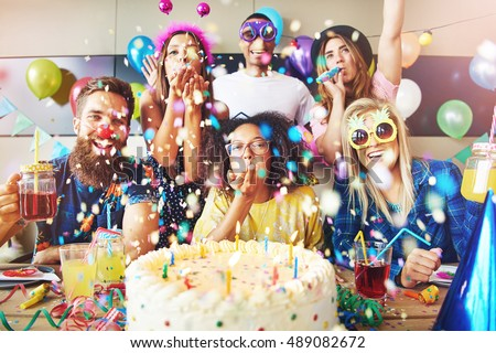 Confetti flying around group celebrating a party with large cake and drinks on table in front of them Foto stock ©