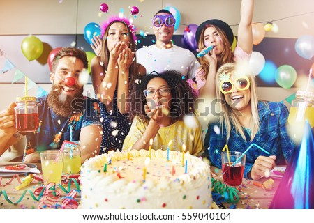Confetti flying around group of cheerful friends celebrating a party with large cake and drinks on table in foreground