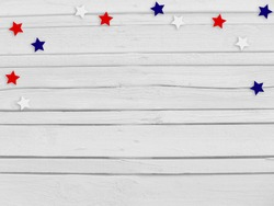 Confetti stars on wooden background. 4th July, Independence day, card, invitation in usa flag colors. Top view, empty space.