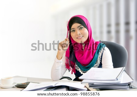 Confidence and smiles of young busy muslim businesswoman while working