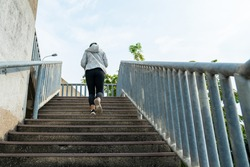 Confidence Asian woman in sportswear running up the stairs in the city. Healthy female athlete enjoy healthy outdoor lifestyle do sport training workout exercise fitness jogging in summer morning
