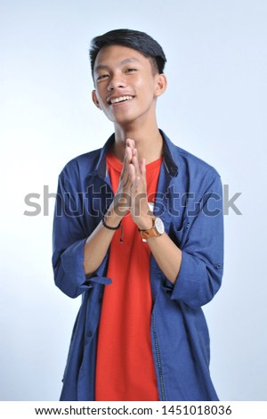 Confidence Asian young man wear casual t-shirts with confident smiling over the grey background