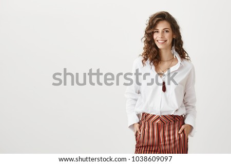Confidence is new sexy. Portrait of charming curly-haired woman in trendy garment smiling broadly and glancing at camera while discussing new plan for today with team over gray background.