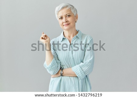 Confidence, people, success and career concept. Studio shot of woman professional in her sixties looking at camera with confident smile, dressed in stylish blue shirt, making gesture with index finger