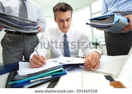 Confident accountant doing financial reports being surrounded by business partners with huge piles of documents