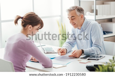 Confident advisor meeting with a customer in his office, he is explaining a contract document and policy to the woman sitting at his desk Foto stock ©