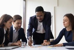 Confident African American businessman hold lead meeting with diverse colleagues in office. Multiracial businesspeople brainstorm discuss company financial paperwork at briefing. Teamwork concept.