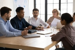 Confident african american businessman talking with young and mature colleagues in boardroom at meeting. Black coach mentor speak with partners negotiating about business project at conversation.