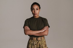 Confident african american soldier woman posing with arms crossed isolated over grey wall
