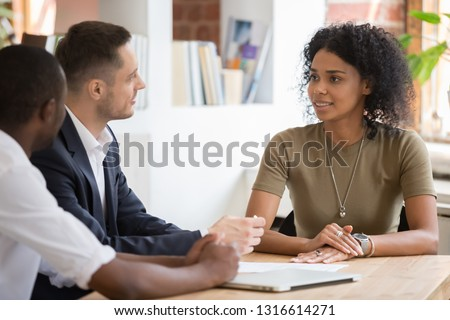 Confident african black female applicant talking to diverse hr managers recruiters at job interview, recruiting team listening to candidate woman making good impression, employment and hiring concept