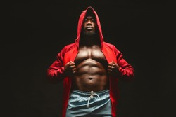 Confident african bodybuilder in red hooded shirt with bare chest, black studio background