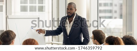 Confident African business coach gives presentation on flip chart, consults clients, teach employees, explain corporate strategy at seminar concept. Horizontal photo banner for website header design Foto stock ©