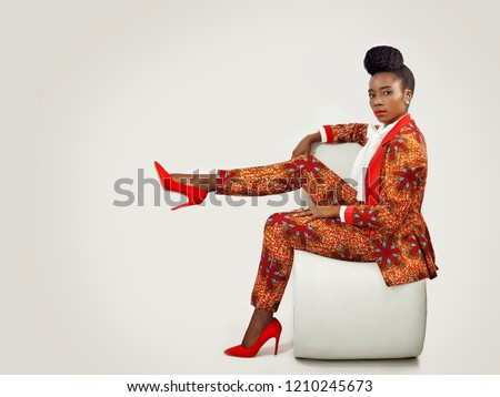 Confident African business woman  wearing an African print suit and heels with a sophisticated hair style sitting in a clean space with her leg propped up.