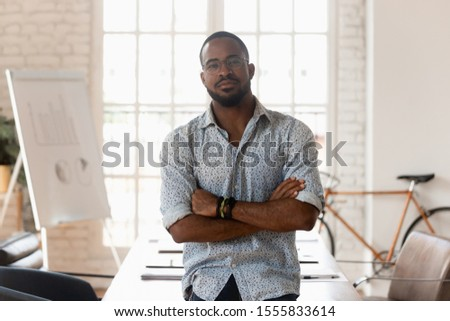 Confident african businessman in glasses casual clothes posing with arms crossed inside modern boardroom office, shooting for company business catalogue, leadership and successful entrepreneur concept