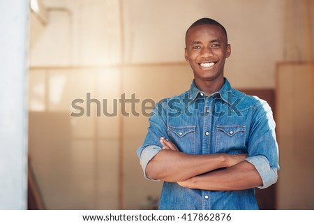 Confident African designer standing proudly in his new studio space
