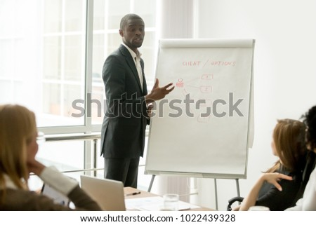 Confident african speaker gives presentation to multiracial sales team with flipchart, black businessman in suit presenting new marketing project speaking at seminar, business coach training managers