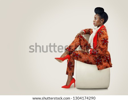 Confident African woman wearing an African print business suit sitting with her legs crossed looking forward.