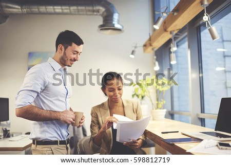 Confident afro american female entrepreneur reading financial report made by skilled professional male accountant discussing advantages and disadvantages during informal meeting in office indoors