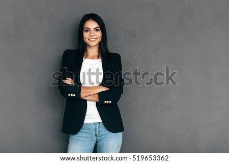 Confident and beautiful. Attractive young woman in smart casual wear keeping arms crossed and looking at camera with smile while standing against grey background #519653362