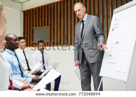 Confident and experienced financier pointing at one of papers on whiteboard and explaining financial statistics to young economists #772048894