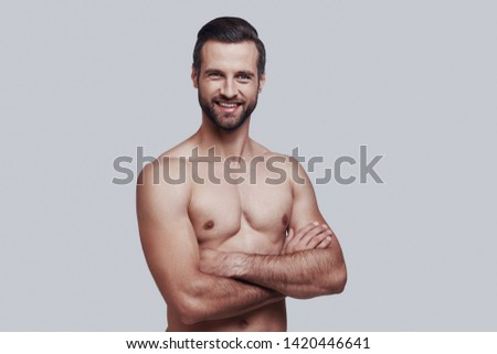 Confident and handsome. Handsome young man looking at camera and smiling while standing against grey background #1420446641