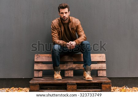 Confident and handsome. Handsome young man sitting on the wooden pallet and looking at camera with grey wall in the background and orange fallen leaves on the floor