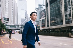 Confident and presentable Asian businessman in strict blue suit and neat pink shirt crossing road in city center near bus stop