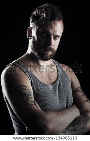 Confident and serious young man / rocker with ear rings.