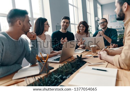 Confident and smart. Group of young modern people in smart casual wear discussing something and smiling while working in the creative office