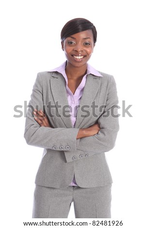 Confident and smiling in grey business suit, a portrait shot of beautiful young black business woman, standing with arms folded.