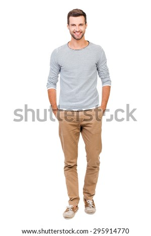 Confident and stylish. Full length of cheerful young man holding hands in pockets and looking at camera while standing against white background
