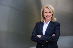Confident and successful CEO business woman in a suit with arms folded