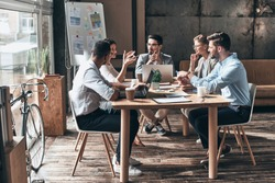 Confident and successful team. Group of young modern people in smart casual wear discussing business while sitting in the creative office
