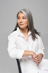 confident asian woman with grey hair sitting on chair isolated on grey