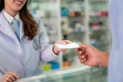 Confident Asian young female pharmacist with a lovely friendly smile and receive medicine prescription from man patient in the pharmacy drugstore. Medicine, pharmaceutics, health care