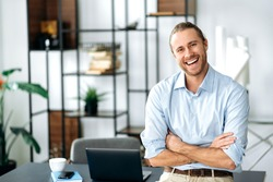 Confident attractive caucasian stylishly dressed guy, ceo, freelancer or employee, standing near his desk, with arms crossed, looking at the camera and smiling friendly