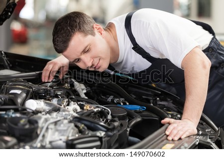 Confident auto mechanic Confident mechanic listening to the car engine working