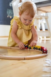 Confident baby girl in yellow dress playing wooden train railways Maria Montessori ecological materials. Cute female toddler enjoying happy childhood with eco friendly playthings at home kindergarten