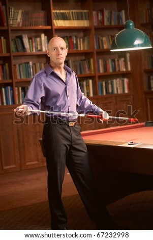 Confident bald man with pool stick in billiards room