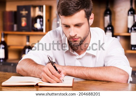 Confident bar owner. Confident young male bartender in white shirt leaning at the bar counter and writing something in note pad