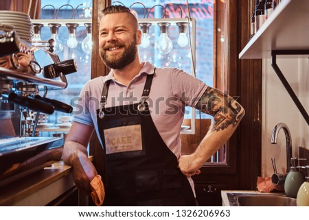 Confident barista with stylish beard and hairstyle wearing apron smiling and looking sideways while leaning on a counter in the cafe or restaurant
