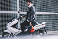 Confident bearded biker dressed in leather jacket standing near white motorcycle with powerful motor in urban setting.Young man with red helmet in hand looking straight near cool motorbike