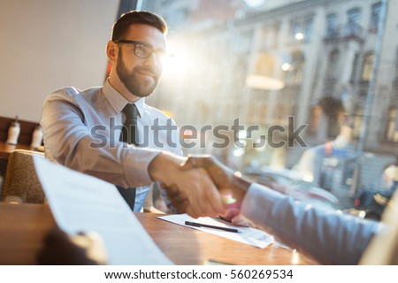 Confident bearded businessman in eyeglasses sitting at cafe table and shaking hand of his partner and smiling after making profitable agreement.